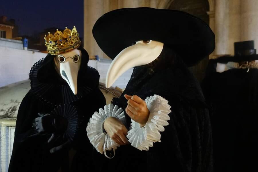 Longs habits noirs et masques blancs à grand nez, le costume pour exorciser le fléau.