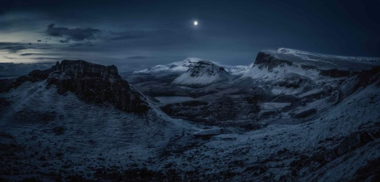Pleine lune au-dessus du Quiraing, une formation géologique d'origine volcanique, dans la péninsule de l'île de Skye en Écosse.