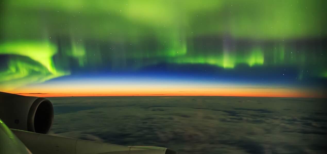 Une aurore boréale capturée à travers le hublot d'un avion