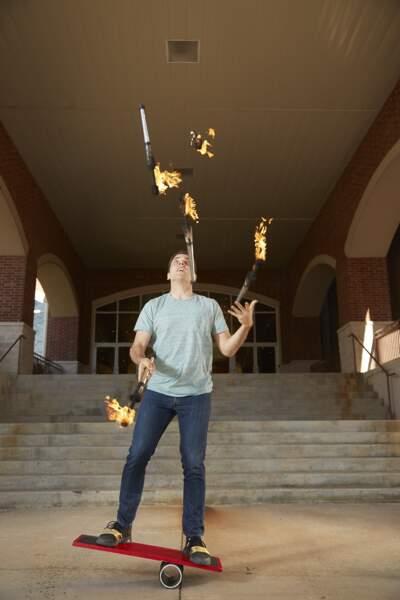 Le jonglage du plus grand nombre de torches sur une planche d'équilibre