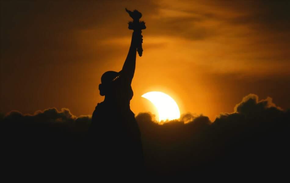 Le soleil se lève pendant l'éclipse solaire partielle, à côté de la statue de la Liberté à New York